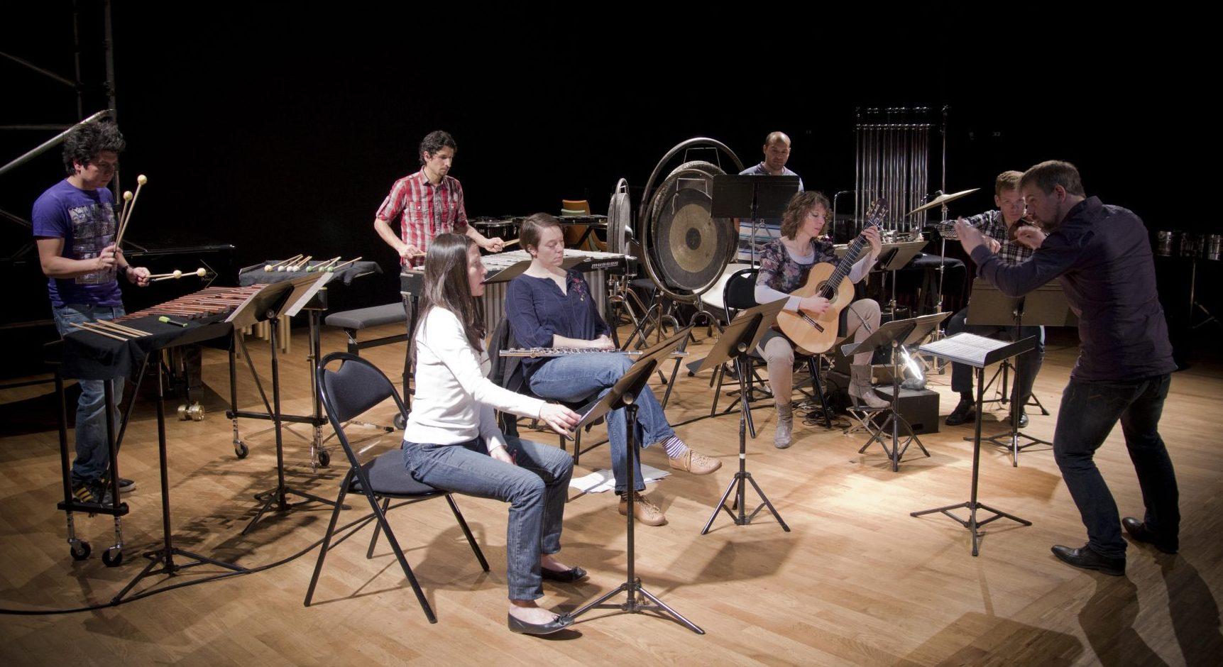 Optreden van Ensemble Insomnio. Dirigent en zeven musici.