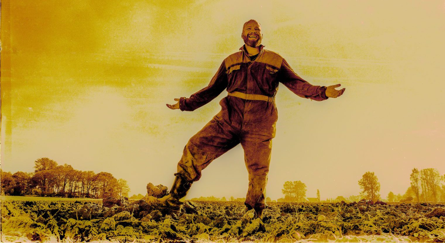 portret van een lachende boer in overall, armen gespreid en met zijn laarzen in de klei