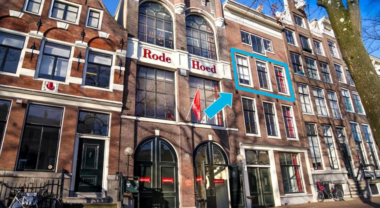 het gebouw van De Rode Hoed aan de Keizersgracht, met een blauwe pijl die drie omlijste ramen op de tweede verdieping aanwijst