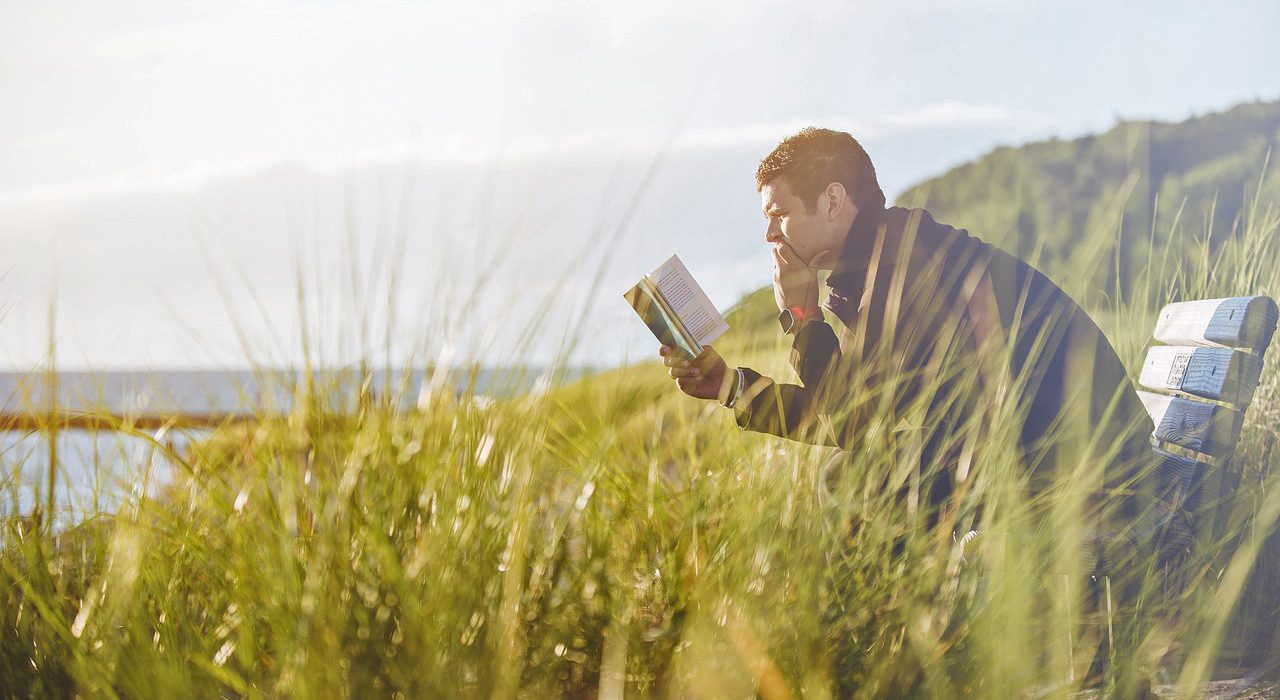 Jongeman die buiten op een bankje in de natuur geconcentreerd zit te lezen in een boek