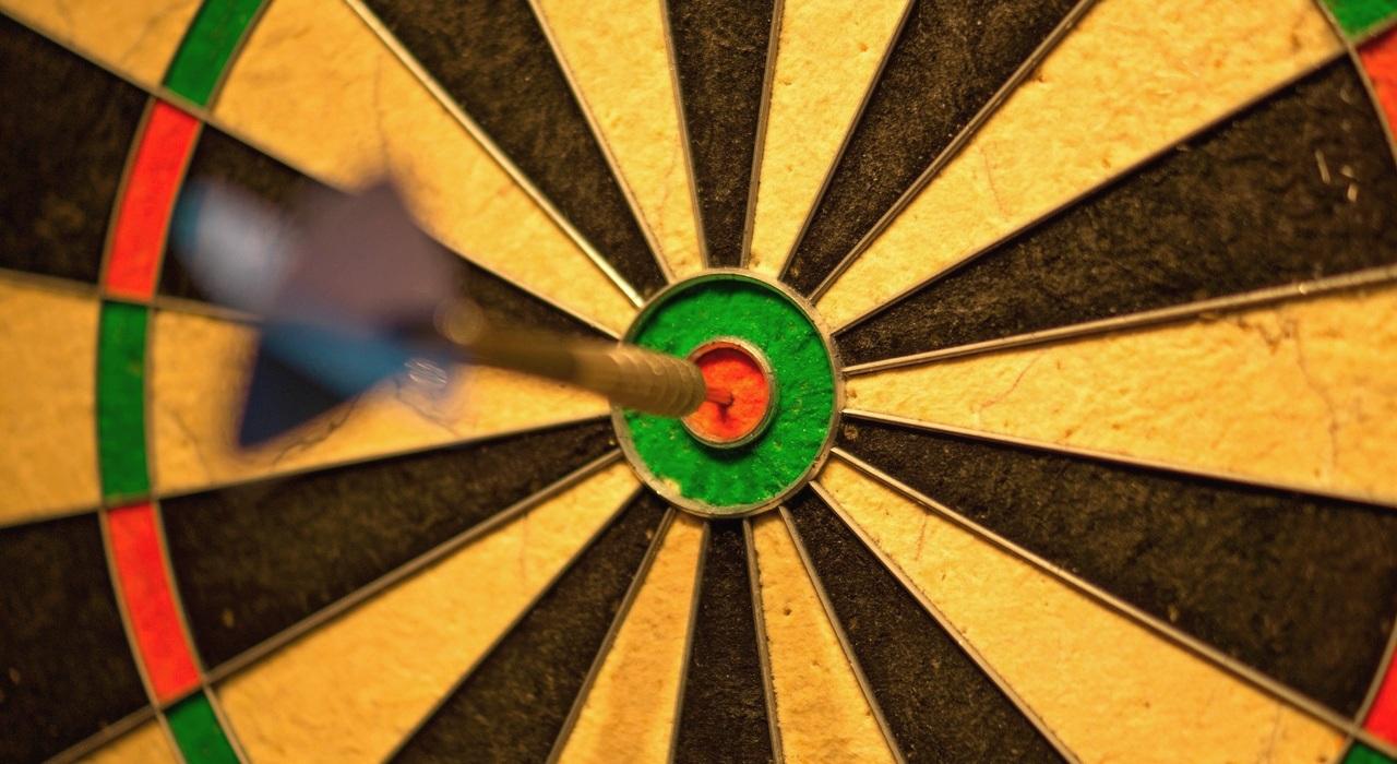 dart-pijl in de roos van een dart-bord