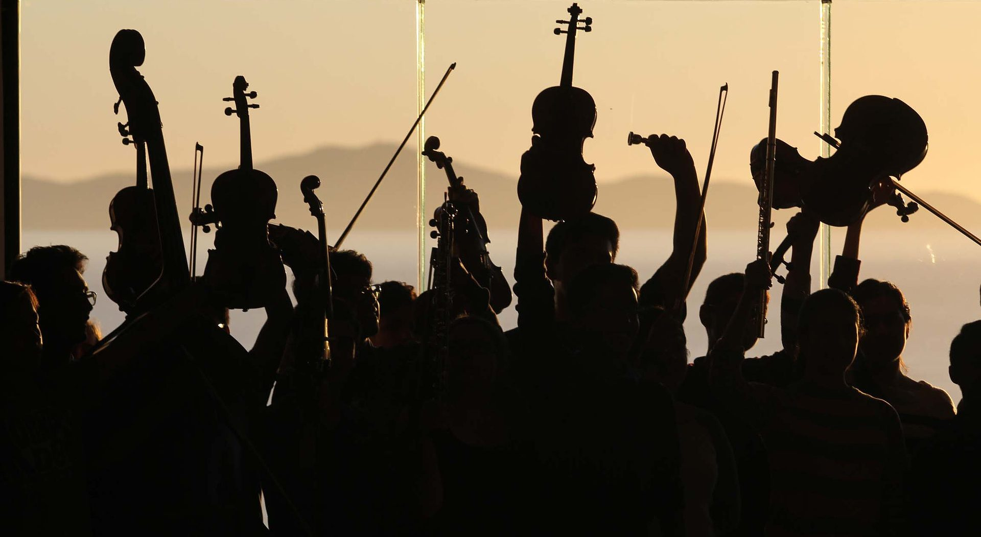 foto van een groep musici die enthousiast hun instrument omhoog houden