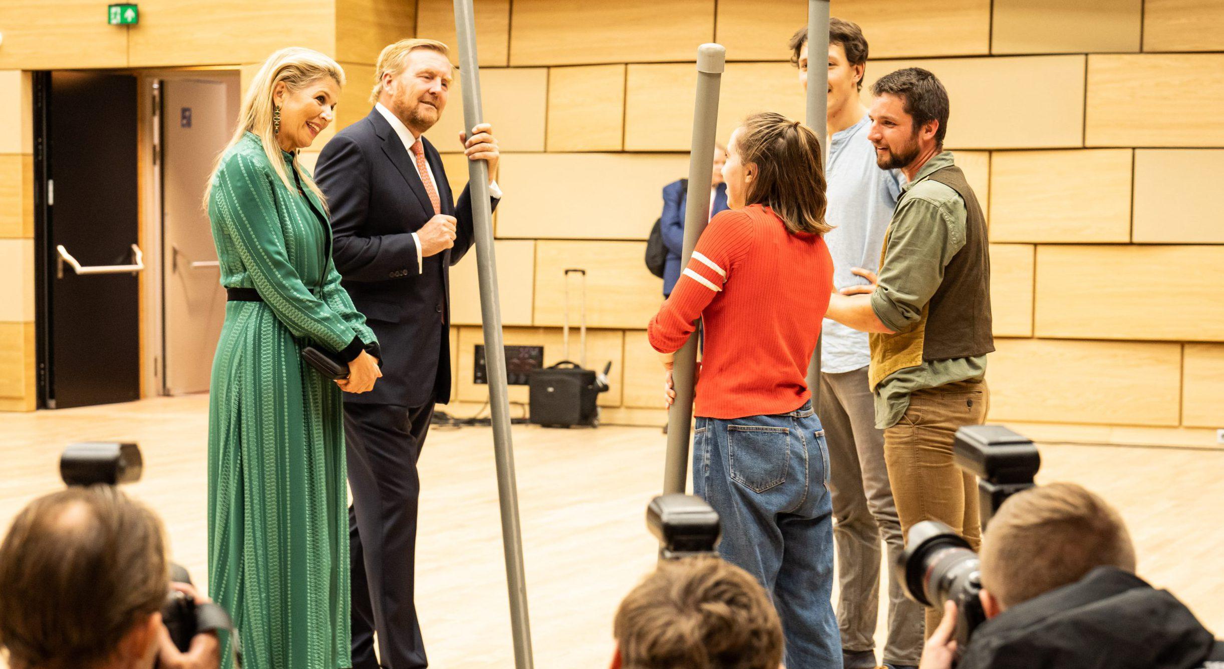 foto van Koning Willem Alexander en Koningin Maxima die spreken met een drietal medewerkers in de concertzaal van Amare. Persfotografen op de voorgrond.