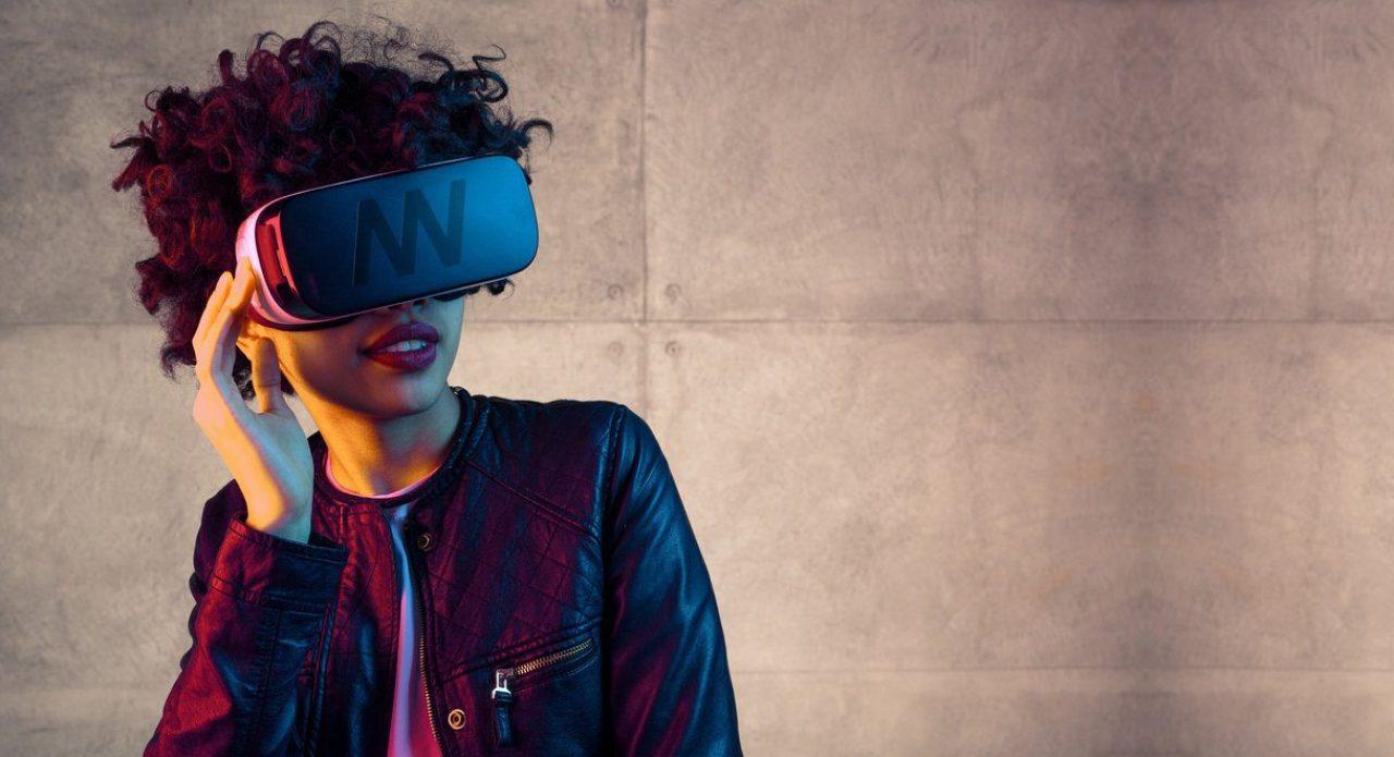 Trendy jonge vrouw in leren jack die met een grote VR-bril poseert voor een betonnen muur