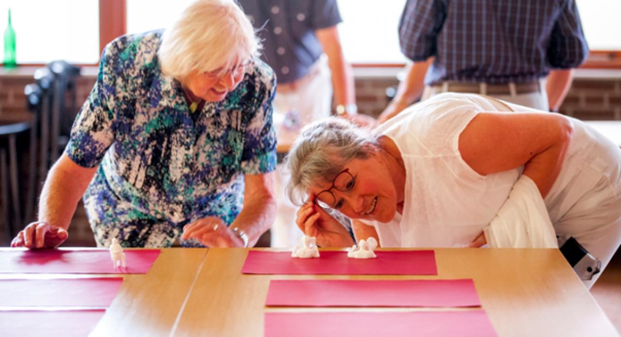 Twee oude dames kijken zorgvuldig naar een tafel waar een aantal boetseerwerkjes op rode vellen papier gezet zijn